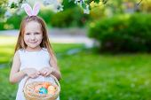 foto of joy  - Adorable little girl wearing bunny ears holding a basket with Easter eggs in a blooming garden on spring day - JPG