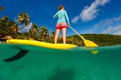 Split underwater photo of young woman on tropical beach vacation paddling on stand up board