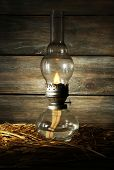 Kerosene lamp with hay on rustic wooden planks background