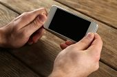 Hands holding smart mobile phone on wooden table background