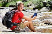 Tablet computer man hiker relaxing by river holding ebook reader reading e book or map, hiking in Yosemite, USA using travel app or map during hike.