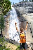 Happy hiking man cheering in success or freedom by waterfall in Yosemite national park. Winner hiker enjoying view of beautiful summer nature landscape, California, USA.