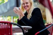 Mature woman drinking cup of coffee in city cafe