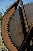 stock photo of osha  - A huge old dangerous rusty circular saw with a safety guard is used to cut logs for firewood - JPG