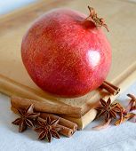 Ripe Red Pomegranate with Spaces on the Wooden Cutting Board