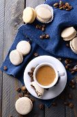 Gentle colorful macaroons and  coffee in mug on wooden table background, top view