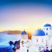 Oia town on Santorini Greece at sunset. Traditional and famous white houses and churches with blue domes over the Caldera, Aegean sea