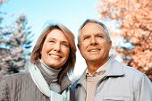 Happy senior loving couple over park nature background