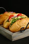 Sandwiches with salmon on tray, on dark background