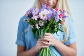 Young female smelling fresh floral bouquet