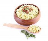 Rice with walnuts and rosemary in plate isolated on white