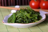 Seaweed salad in plate with bamboo on background