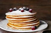 Stack of delicious pancakes with powdered sugar and berries on plate and napkin on wooden background