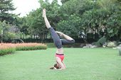 Young Woman In Headstand Yoga Pose On Lawn