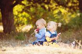Постер, плакат: Small children a boy and a girl playing in the Park on the grass