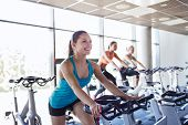 sport, fitness, lifestyle, equipment and people concept - group of women riding on exercise bike in gym