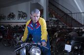 Middle Aged Man Placing A Motorbike.