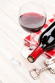 Red wine bottle, glass and corkscrew on white wooden table background with copy space