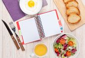 Healthy breakfast with fried egg, toasts and salad on white wooden table with notepad for copy space