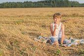 Teenage Boy In Farm Field With Glass Of Milk