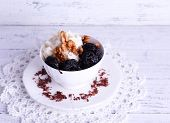 Dessert with prunes and nuts in cup on lace doily on color wooden background