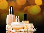 Cosmetics and roses on bright festive background