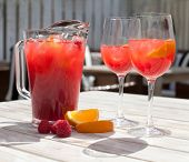 Raspberry Lemonade: Two Glasses, Pitcher, Raspberries On The Table. Sunshine. Shadows. White Wooden