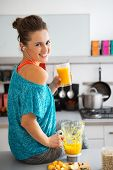 Portrait Of Happy Fitness Young Woman With Glass Of Pumpkin Smoothie In Modern Kitchen