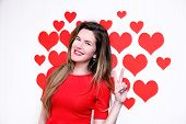 White caucasian woman with red lips giving a counting hand (two sign) on a heart shaped background.V