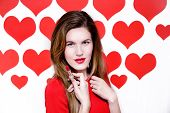 White caucasian woman with red lips holding a red lipstick on heart shaped background.Valentine`s da