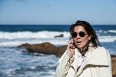 Attractive Woman On Seashore Talking On The Phone