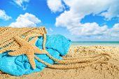 Beach bag lying on sand with towel and starfish