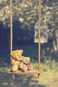Two teddies on rustic swing in the orchard with vintage tone effect
