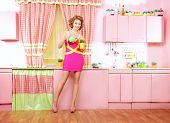 Pretty woman on her pink kitchen at home. Beauty, fashion.