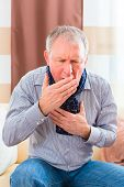 stock photo of cough  - Old man coughing and holding breast having a bad cold  - JPG