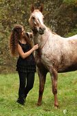 pic of appaloosa  - Beautiful girl with nice dress standing next to nice horse in autumn