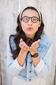 Pretty hipster blowing a kiss against bleached wooden fence