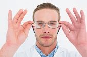 Optician in coat holding glasses on white background