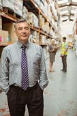 Cheerful businessman with hands in pocket posing in a large warehouse