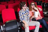 Young couple watching a 3d film at the cinema
