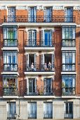 Young Girls On Balconies Of A Typical Building Facade On A Street Of Madrid, Spain