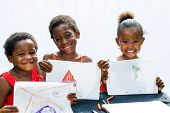 Three African Youngsters Showing Their Drawings.