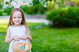 image of bunny costume  - Adorable little girl wearing bunny ears holding a basket with Easter eggs in a blooming garden on spring day - JPG
