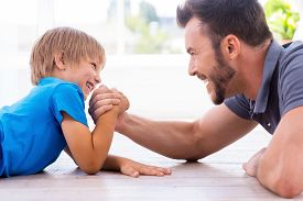 pic of competing  - Side view of happy father and son competing in arm wrestling while both lying on the hardwood floor  - JPG