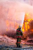 foto of fire extinguishers  - Fireman extinguishes a fire in an old wooden house - JPG