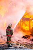 image of firemen  - Fireman extinguishes a fire in an old wooden house - JPG