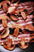 stock photo of bacon strips  - Strips of bacon with mushrooms in pan - JPG