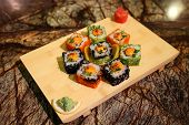 stock photo of na  - Delicious sauced Saka na maki sushi rolls served with a wood plate - JPG