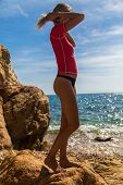 picture of string bikini  - Sexy girl standing on the cliff of the rocky beach of Costa Brava - JPG