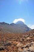 stock photo of greek-island  - Red dusty road in the mountains on the Greek island - JPG